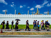 27 SEPTEMBER 2017 - BANGKOK, THAILAND:  Tourists walk past the Grand Palace on their way to the palace gate. The Royal Household has announced that the palace will close to the public, including tourists, on 04 October 2017 to allow officials to complete preparations for the cremation of Bhumibol Adulyadej, the King of Thailand, who died on 13 October 2016. They also extended the official mourning period by 15 days. It was originally set to end on 13 October 2017 but now will end on 26 October 2017, the day of the King's cremation.    PHOTO BY JACK KURTZ