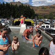 Youngsters cool off in the back of a truck filled with water to create a swimming pool during the 50th Anniversary Glenorchy Race meeting. The races, which originally started in the 1920's, were resurrected in 1962 and have been run by local farmers and the rugby club on the first Saturday after New Years Day ever since. Glenorchy, Otago, New Zealand. 7th January 2012