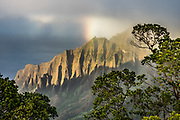 A rainbow shines over cliffs above the Pacific Ocean at Kalalau Valley on the Na Pali Coast at Kalalau Lookout, Kokee State Park, Kauai, Hawaii, USA. The scenic Koke'e State Park is in northwestern Kauai in the Hawaiian Islands. Perched on a plateau between 3200 and 4200 feet, the park gets temperatures at least 15 degrees Fahrenheit cooler than at sea level. Koke'e receives 50-100 inches of rain per year, mostly from October to May. Its forests are dominated by Acacia koa and ohia lehua (Metrosideros polymorpha) trees.