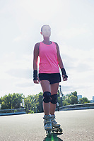 Portrait of young attractive woman wearing rollerblades