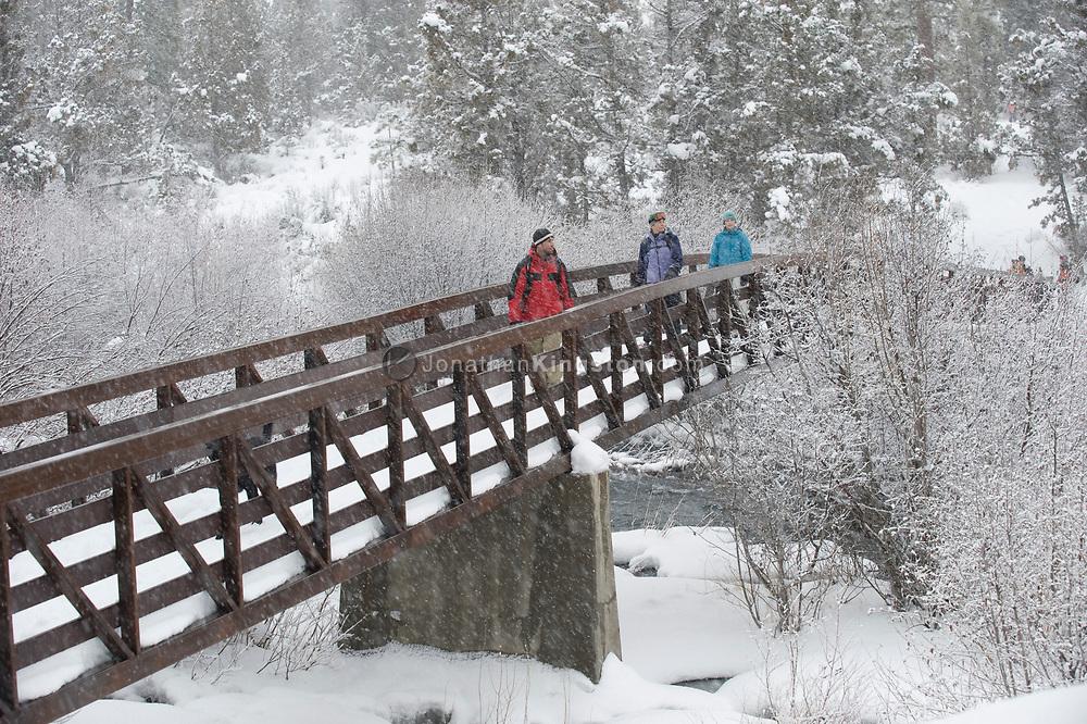 Front view of three adults walking across a pedestrian bridge across a river covered in snow in Bend, Oregon. (releasecode: jk_mr1036, jk_mr1032, jk_mr1031) (Model Released)