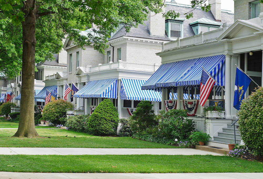 White brick homes with American flags and blue and white striped awnings on the grounds of the US Naval Academy, Annapolis, Maryland.