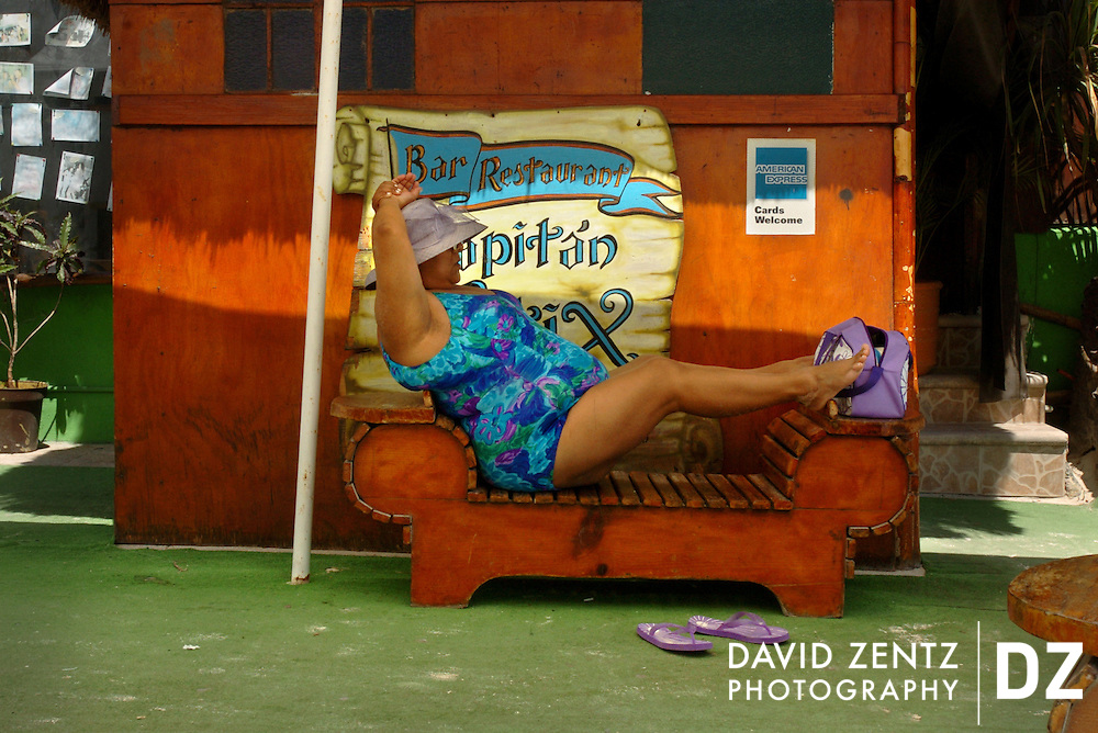 A woman tourist rests her feet on a bench outside the popular tourist bar, Captain Tutix, in Playa del Carmen, Mexico, one of the fastest growing cities in the western hemisphere, on March 9, 2004.