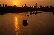 The sun rises over the River Thames and City of London, the UK capital's financial heart. The solar power gathers in strength and intensity as it climbs from below the horizon and behind City buildings, its circular disc a flaming yellow which is soon to turn a deeper hue over the capital's orange skies at dawn. The tidal river is calm with only moored barges in the middle, used to secure other boats to their sides. The City wakes before another day of trading in the financial, banking and insurance institutions. The dome of St Paul's Cathedral is centre to the skyline.