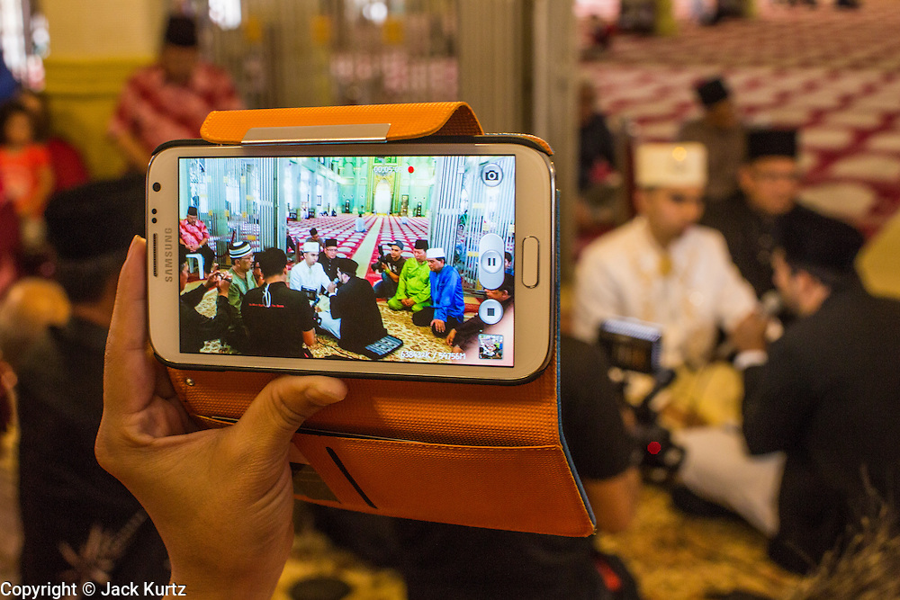 22 DECEMBER 2012 - SINGAPORE, SINGAPORE: A wedding guest records video of a wedding on his smart phone at the Sultan Mosque in Singapore. The Sultan Mosque is the focal point of the historic Kampong Glam area of Singapore. Also known as Masjid Sultan, it was named for Sultan Hussein Shah. The mosque was originally built in the 1820s. The original structure was demolished in 1924 to make way for the current building, which was completed in 1928. The mosque holds great significance for the Muslim community, and is considered the national mosque of Singapore. It was designated a national monument in 1975.           PHOTO BY JACK KURTZ