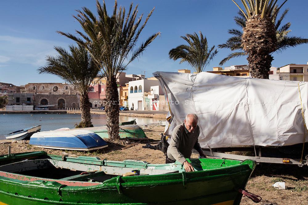 Lampedusa, Italia - Giuseppe Mercurio, pescatore pensionato vernicia la sua barca.<br /> Ph. Roberto Salomone