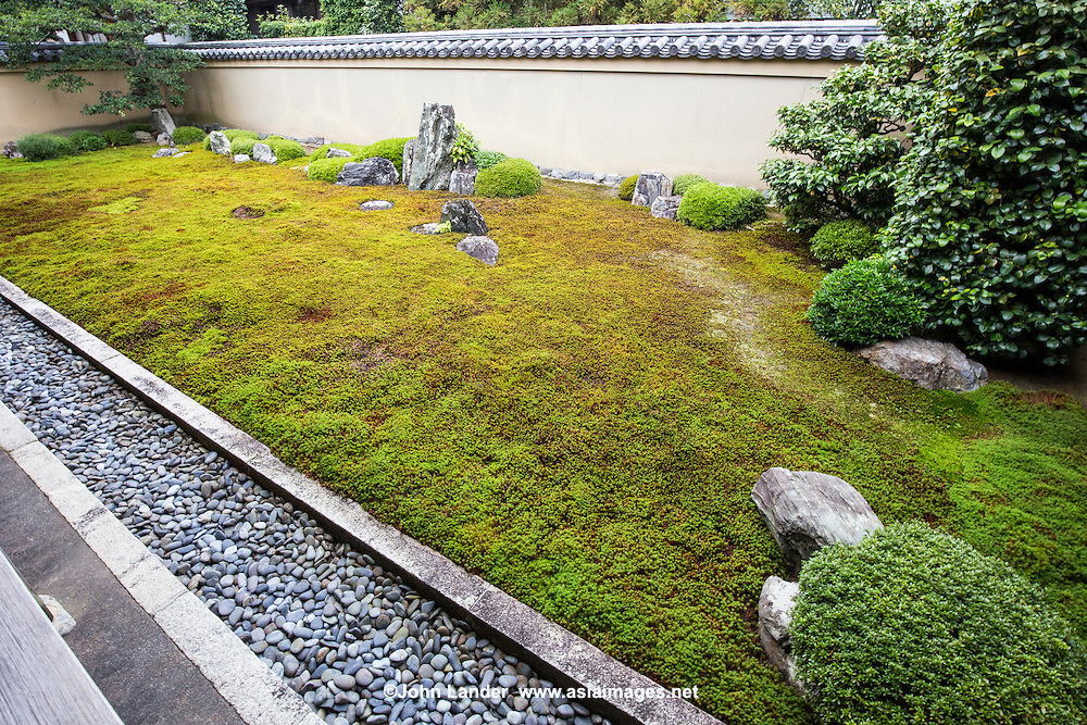 """Ishidani"" is made up of moss and stones.  The largest patch represents a turtle, while the two smaller standing stones in the back make up ""Crane island"" -  These two animals are often depicted in zen gardens. The two large standing stones represent a mountain: Horaizan."