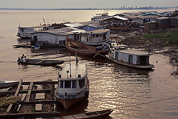 BRAZIL - Amazon region of Brazil: The Amazon river basin is located mainly (50%) in Brazil, but also stretches into Peru and several other countries. The South American rain forest of the Amazon is the largest in the world, covering about 8,235,430 sq km with dense tropical forest. For centuries, this has protected the area and the animals residing in it. The Amazon is bounded by the Guiana highlands in the north and the Brazilian highlands in the south. The Amazon, which rises in the Andes Mountains at the west of the basin, is the second largest river in the world. It covers a distance of about 6,400 km before draining into the Atlantic Ocean. The Amazon and its tributaries form the largest volume of water. The Amazon accounts for about 20% of the total water carried to the oceans by rivers. Most people in the Amazon region live off fishing and basic agriculture, and especially in the southern part of the Brazilian side, cattle herding, which is extremely destructive of the forest. One important exception is the Zona Franca de Manaus (Free Zone of Manaus), created by the Brazilian government in the 1970s to implement light industries in the region, mostly electronics and motorcycles. Contrary to what might be believed, this light industrialization is very little pollutive and actually, according to some environmentalists, has helped save the rainforest around Manaus by creating job opportunities and education, thus driving people away from the heavily damaging subsistence and slash-and-burn agriculture.