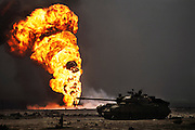 An abandoned Iraqi tank in front of the burning Magwa oil fields in Kuwait after the end of the Gulf War in 1991. The desert was covered in oil that rained down from the clouds of oil smoke and oil shooting into the air after a fire had been extinguished. More than 700 wells were set ablaze by retreating Iraqi troops creating the largest man-made environmental disaster in history.