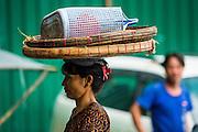 12 JUNE 2013 - YANGON, MYANMAR:   A woman carries a basket on her head in Yangon, Myanmar.        PHOTO BY JACK KURTZ