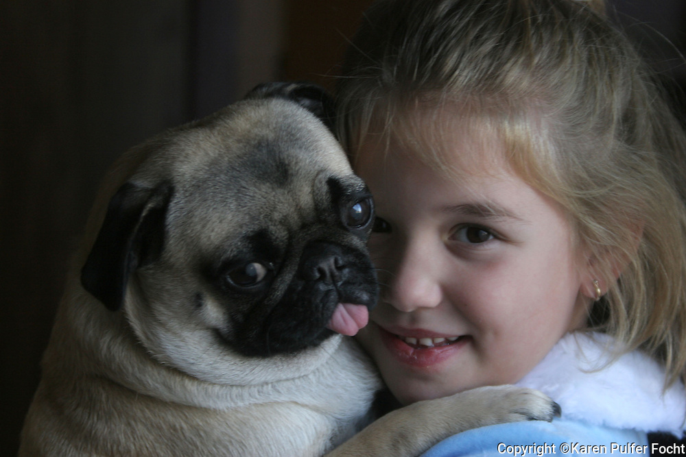 Elli Rose Focht and her companion, Peppermint the pug. Pugs are great dogs for children as they tend to be very tolerant and gentle.