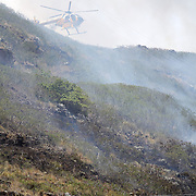 Air One approached through heavy smoke to review the brushfire before it made water drops.  HFD firefighters battled to contain a Hawaii Kai, Oahu brushfire before it crosses over the ridge from Pepeekeo St. to Kawaihae Dr and the condos below.  Photo by Barry Markowitz, 9/4/13, 11:45am