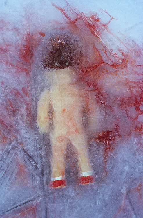 Doll lying face down in ice and surrounded by blood