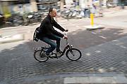 Een man rijdt op een vouwfiets door het centrum van Utrecht.<br /> <br /> A man is riding a folding bike in Utrecht.