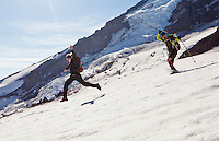 A young man and woman run and leap down the Muir snow field on Mount Rainier, Washington, USA.