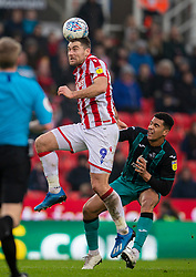 STOKE-ON-TRENT, ENGLAND - Saturday, January 25, 2020: Stoke City's Sam Vokes (L) challenges for a header with Swansea City's Ben Cabango during the Football League Championship match between Stoke City FC and Swansea City FC at the Britannia Stadium. (Pic by David Rawcliffe/Propaganda)