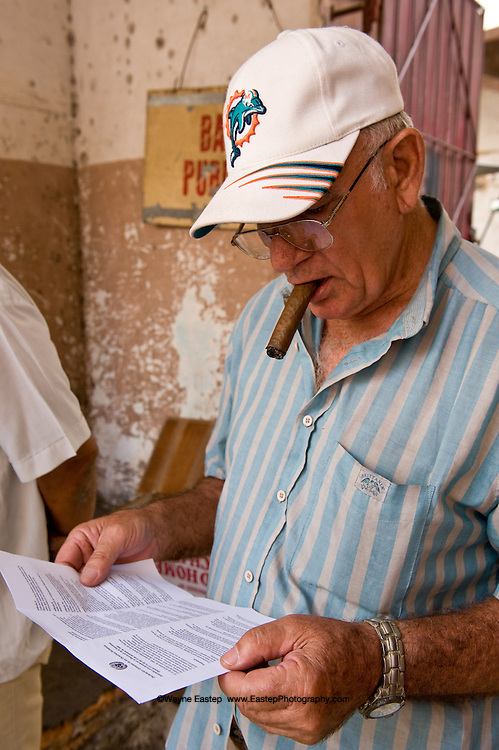 Saturday, March 1, 2008:  wearing a Dolphins cap, smoking a Cuban cigar, this Havana resident reads a copy of the Declaration of Human Rights handed out on Neptuno Street.  United Nations, February 28, 2008:  Cuban Foreign Minister, Felipe Perez Roque, signed two legally binding covenants of the Declaration of Human Rights.