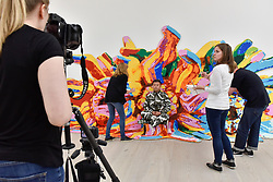 """© Licensed to London News Pictures. 13/09/2017. London, UK. Renowned Chinese artist Liu Bolin begins his new work """"The Disappearing Act"""", the world's first ever live time-based performance in the context of an art fair.  Taking place during the START Art Fair at the Saatchi Gallery, Chelsea, specially chosen local artists are being directed to help Bolin disappear into the background of Lego bricks which depict a sunflower.  Photo credit : Stephen Chung/LNP"""