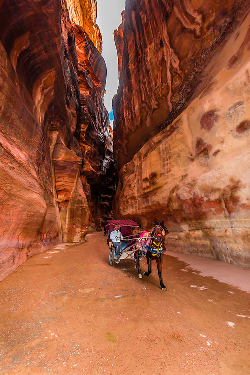 Horse drawn carriage riding through the Siq (a 1200 meter long gorge) in the Petra archaeological site (a UNESCO world heritage site), Jordan.