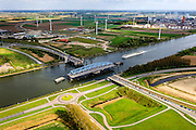 Nederland, Zeeland, Zeeuws-Vlaanderen, 09-05-2013; Sluiskil, Kanaal Gent-Terneuzen, kanaalkruising Sluiskil. De brug in de N61 sluit zeer regelmatig voor zeeschepen en dit veroorzaakt files. Daarom zal de kanaalbrug vervangen worden door een tunnel, de Sluiskiltunnel (oplevering 2015). <br /> Stikstofbindingsbedrijf Yara, fabricage van kunstmest, ammoniak, ureum, salpeterzuur, CO2 (kooldioxide) in e achtergrond Cruiseschip vaart door de open brug.<br /> The pivot bridge over the canal Gent-Terneuzen (Zeeland) closes very regularly for seagoing vessels and this causes traffic jams. Therefore, the canal bridge will be replaced by a tunnel, the tunnel Sluiskil (completion 2015).<br /> Cruise ship on the canal. Yara, nitrogen compound company manufactures fertilizer, ammonia, urea, nitric acid, CO2 (carbon dioxide) (r,b)<br /> luchtfoto (toeslag op standard tarieven);<br /> aerial photo (additional fee required);<br /> copyright foto/photo Siebe Swart.