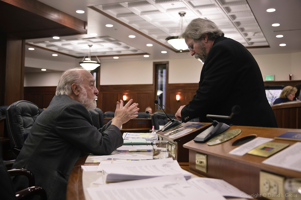 Bob Lynn (R) (left) and David Guttenberg (D) (right) chat in the chambers of the Alaska State House of Representatives.