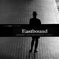 A silhouetted woman standing in front of an EASTBOUND train station sign at an urban train station.