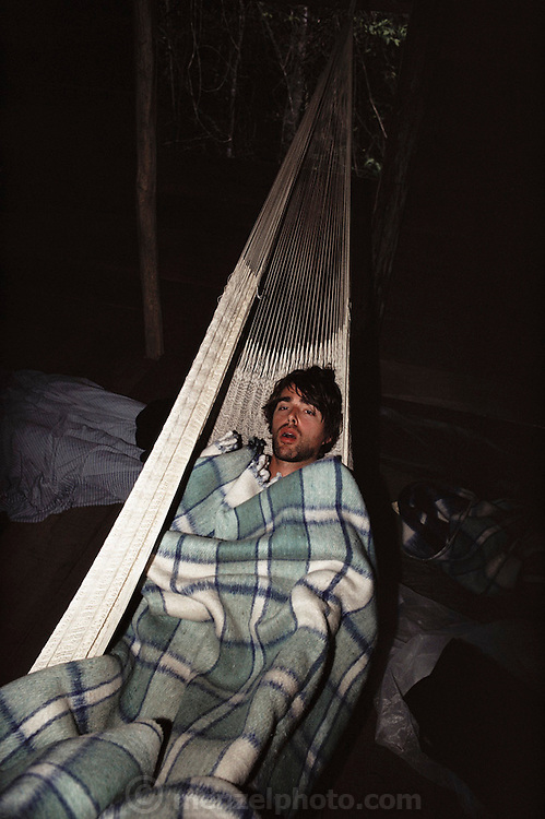 Charles C. Mann, sick and sleeping in a hammock at a jungle camp while visiting the excavation work on the Mayan ruins at Calakmul, Yucatan, Mexico. MODEL RELEASED.