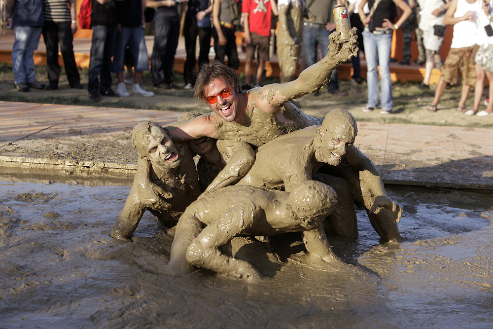 Festival goers jumping into mud. The mud pond was created by students of architecture, evoking the atmsphere of Woodstock on its 40th anniversary. 34th Paleo Festival, Nyon, Switzerland.