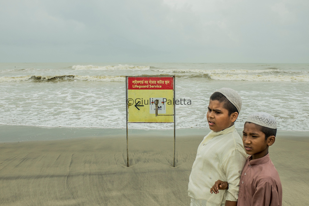 Two kids walk along together on the beach of Cox's Bazar, Bangladesh