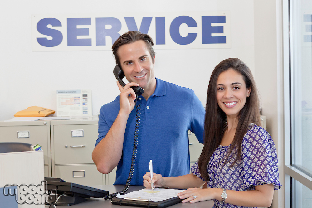Portrait of man and woman standing in auto repair shop