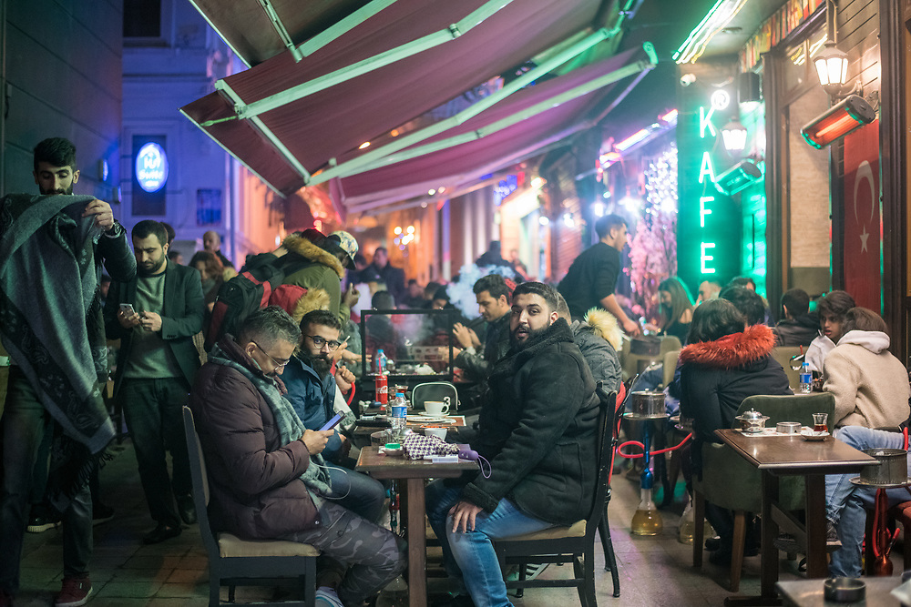 A group of man gather at a table outside of a cafe to enjoy a bite to eat, Istanbul, Turkey