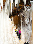 A brother and sister stand in a small ice cave at the Apostle Island Ice Caves, Makwike Bay, near Bayfield, Wisconsin, on a cold February day.