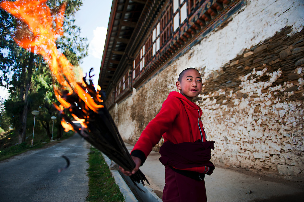 A novice monk is ready with fire to help with work on his Dzong in eastern Bhutan.
