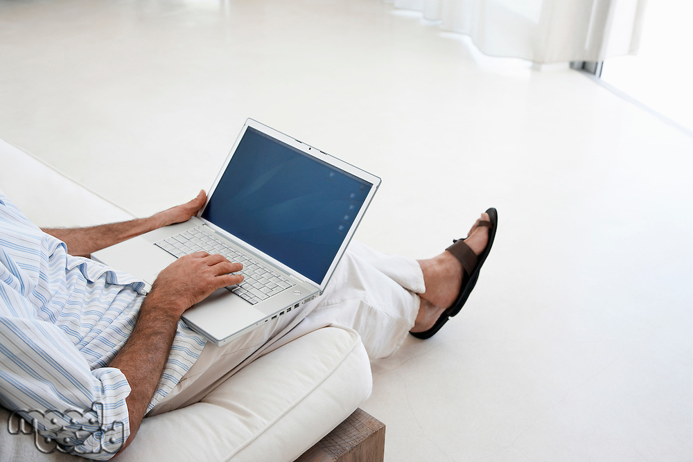 Man using laptop sitting on sofa in living room low section elevated view