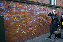 "© Licensed to London News Pictures . 11/01/2014 . Tottenham , London , UK . CAROLE DUGGAN leaves the vigil pasing a wall with anti police graffiti including "" ACAB "" .  Campaigners hold a vigil in memory of Mark Duggan outside Tottenham Police Station this afternoon (11th January 2014) . A jury found Duggan was lawfully killed by police in August 2011 . Duggan's shooting and a protest at the same location in August 2011 sparked riots and several days of looting across London and England . Photo credit : Joel Goodman/LNP"