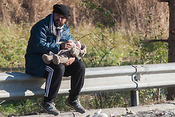 Licensed to London News Pictures. 03/11/2015. Sentilj, Slovenia. Migrants are waiting to enter Austria at the border crossing in Sentilj, Slovenia. Migrant is feeding his baby. Photo: Marko Vanovsek/LNP