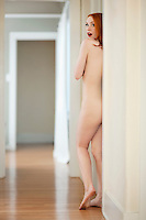 Back view of naked woman hiding behind wall in corridor