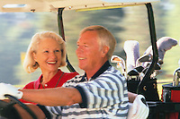 Retired Couple Riding in Golf Cart --- Image by © Jim Cummins/CORBIS