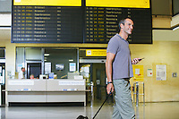 Traveller holding mobile phone in front of flight status board in airport