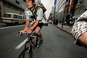 Jun Yajima, a messenger at T-Serv Bike Messenger service, makes a delivery on the busy streets of Tokyo, Japan.  (From the book What I Eat: Around the World in 80 Diets.) MODEL RELEASED.