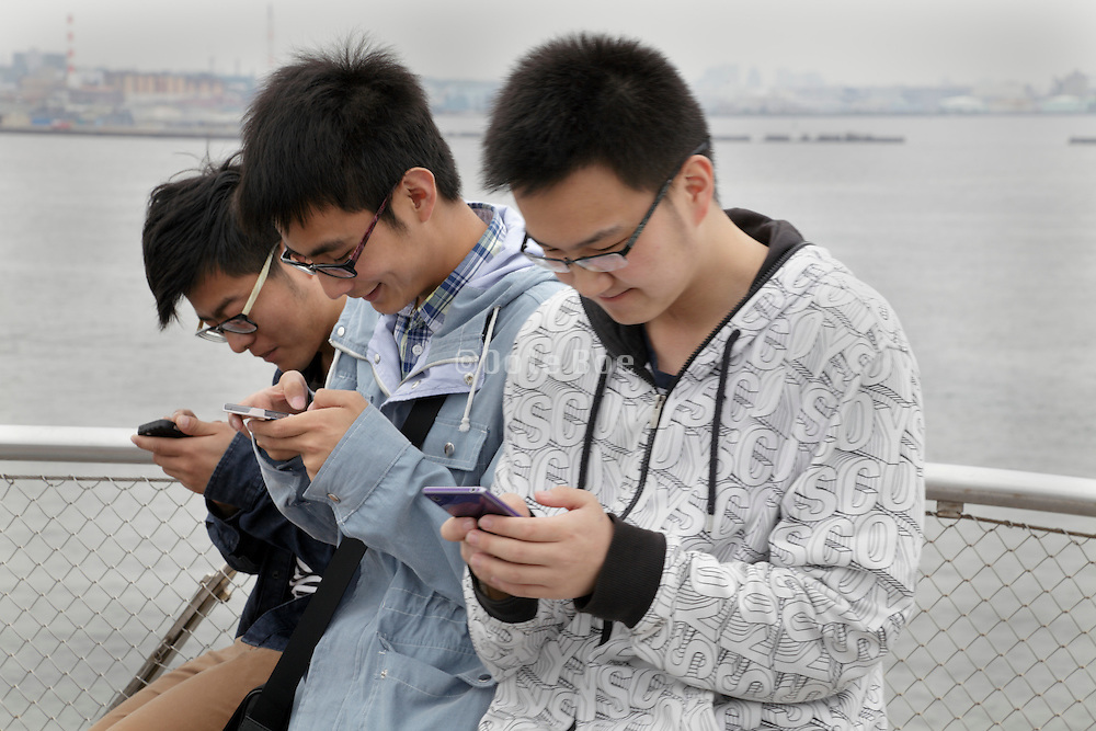 Japanese teenagers absorbed in their smartphones