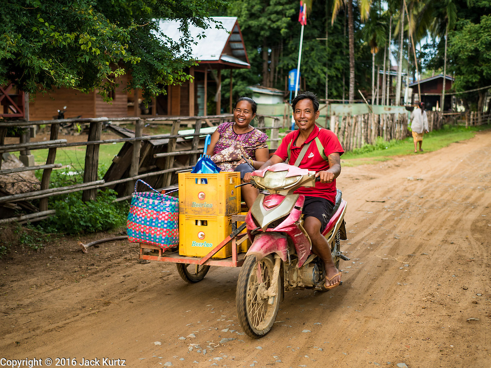 17 JUNE 2016 - DON KHONE, CHAMPASAK, LAOS: A Lao woman rides the local version of a tuk tuk, a three wheeled taxi on Don Khon. There are no cars on the island and most people get around with either tuk-tuks or motorcycles. Don Khon Island, one of the larger islands in the 4,000 Islands chain on the Mekong River in southern Laos. The island has become a backpacker hot spot, there are lots of guest houses and small restaurants on the north end of the island.        PHOTO BY JACK KURTZ