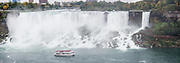 A Hornblower Niagara Cruise boat tours beneath American Falls and Bridal Veil Falls. The town of Niagara Falls in Ontario, Canada, gives excellent views of all three sections of Niagara Falls, which drops 167 feet (51 m). Niagara Falls has the highest flow rate of any waterfall in the world. Niagara Falls is the name for the combined flow of Horseshoe Falls, American Falls and Bridal Veil Falls, on the Niagara River along the international border between Ontario, Canada and New York, USA. The Niagara River drains Lake Erie into Lake Ontario. Horseshoe Falls is the most powerful waterfall in North America, as measured by vertical height combined with flow rate. The falls are 17 miles north-northwest of Buffalo, New York and 75 miles south-southeast of Toronto. The panorama was stitched from 3 overlapping photos.