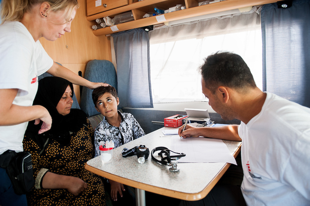 Six year old Mohammed, together with his mother, from Iraq is checked by MSF doctor Dimitris Giannousis and MSF nurse Ida Tornstensson at the mobile camper van of MSF at Mytiline port, Lesvos, Greece.