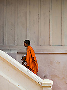 12 MARCH 2016 - LUANG PRABANG, LAOS: A Buddhist monk walks into a temple's meditation hall in Luang Prabang, Laos. Laos is one of the poorest countries in Southeast Asia. Tourism and hydroelectric dams along the rivers that run through the country are driving the legal economy.       PHOTO BY JACK KURTZ