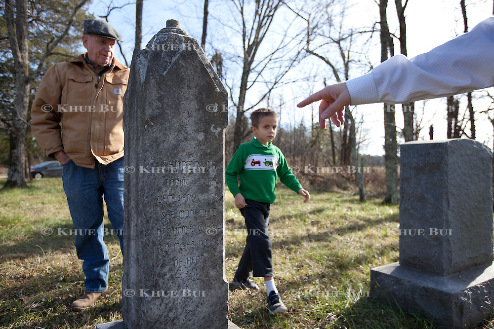 John W. Sanderson (age 75, brown coat); William I. Sanderson &ndash; goes by Bill (age 40, blue fleece vest), son of John W. Sanderson;  Clinton Sanderson Sancho (age 6, green sweatshirt), grandson of John W. Sanderson; visit the private family cemetery Thursday, December 22, 2016, in Cartersville, VA.  The private cemetery contains 4 named graves, but the family believes there are more family members buried here as there are more stones next to the named grave sites.<br /> <br /> Photo by Khue Bui for the New York Times