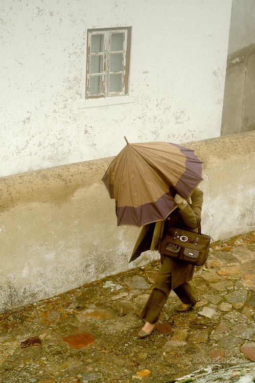 Women trying to walk on a rainy and windy day
