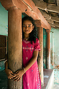 A young girl stands beside a wooden pillar at her home in Tranquebar. Tranquebar was once a Danish Colony.
