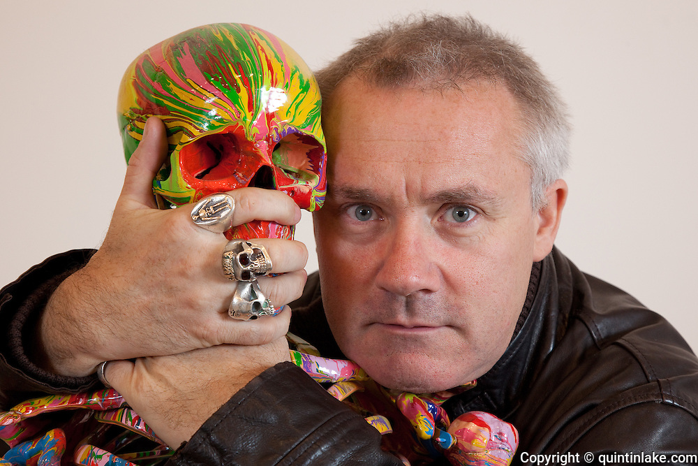"Close-up Damien Hirst Portrait with hands around skull of his artwork.""St Elmo's Fire"".2008.Household gloss on plastic skeleton.1700 x 425 x 435 mm.© Damien Hirst. All rights reserved, DACS 2010.Photographed in his Chalford Studio, near Stroud, Gloucestershire"
