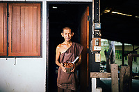 A monk holds out one of the countless ingredients in Tham Krabok's drug rehab elixir, which induces vomiting in the patients at the temple.